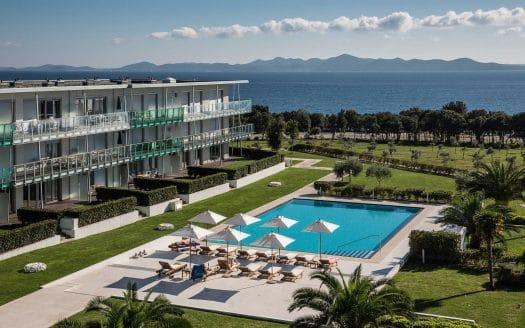 Falkensteiner premium apartments Senia, Aussenansicht mit Pool, im Hintergrund das Meer.