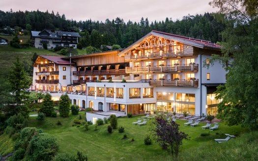Hotel Inntalerhof Aussenansicht im Sommer. Das Hotel liegt eingebettet in viel Grün und die Berge.
