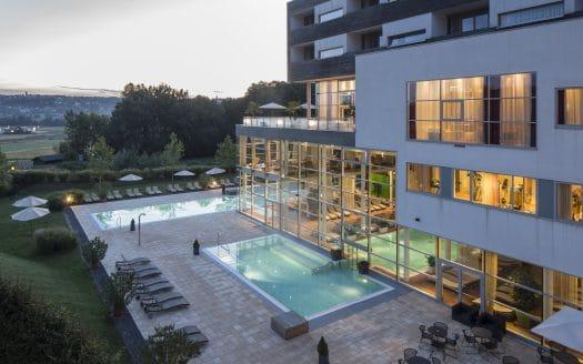Spa Resort Styria Außenansicht mit zwei Pools bei Dämmerung.