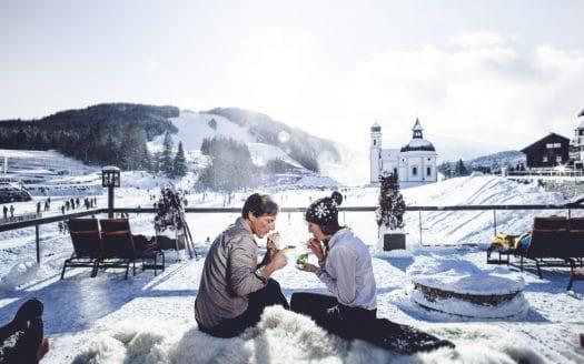 Pärchen in sonniger Winterlandschaft, Hotel Inntalerhof, Winterurlaub mit Hund in Österreich