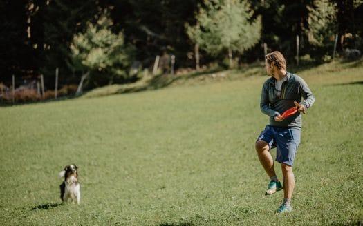 Mensch spielt mit Hund auf der grünen Wiese, Wanderhotel Vinschgerhof, Urlaub mit Hund