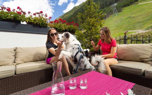 zwei Hunde mit zwei Frauchen auf der Terrasse im Frühling, Hotel Fliana, Urlaub mit Hund in Österreich
