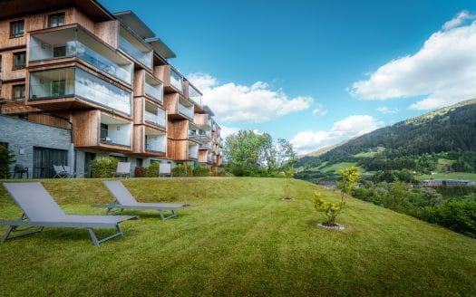 Aussenansicht Sun Lodge mit grüner Wiese und Liegestühlen vor dem Hotel. Im Hintergrund blauer Himmel und Berge.